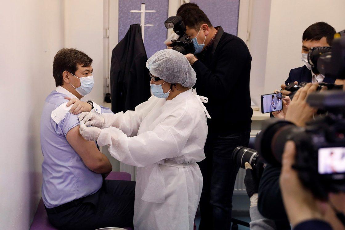 NUR-SULTÁN (KAZAJISTÁN), 01/02/2021.- El médico sanitario jefe de Kazajistán, Yerlan Kiyasov (i), recibe la primera dosis de la vacuna rusa Sputnik V contra el coronavirus en Nur-Sultán, Kazajistán, este lunes. Kazajistán inició este lunes su campaña de vacunación masiva de la población contra la covid-19 con el preparado ruso Sputnik V, anunciaron las autoridades del país centroasiático. En la primera etapa de la vacunación, Sputnik V será suministrada al personal sanitario kazajo. Se espera que durante el mes de febrero reciban la vacuna cerca de 100.000 sanitarios. Los primeros en ponerse la primera dosis del preparado fueron el médico sanitario jefe de Kazajistán, Yerlan Kiyasov, y la viceministra de Sanidad, Azhar Giniyat. EFE/ Holdorbekov Muhtor Turapovich