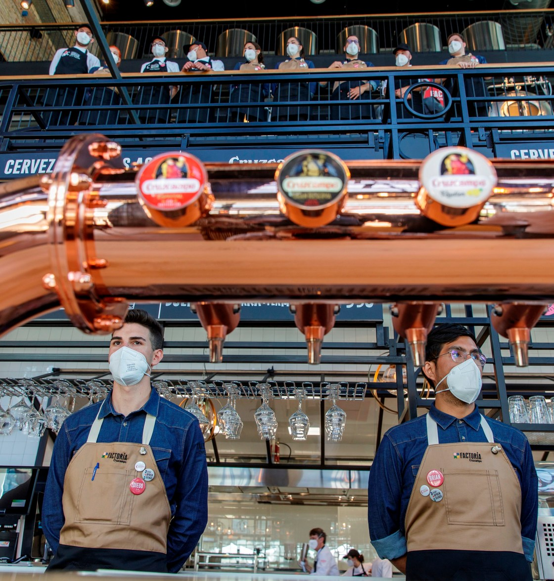 GRAF9552. SEVILLA, 30/05/2021.- Alumnos ante los grifos listos para dispensar cerveza recién salida del proceso artesanal en la Factoría Cruzcampo, donde la Fundación Cruzcampo ha reforzado su compromiso social con este proyecto, que se inaugurará en su antigua fábrica de Sevilla el 1 de junio, y con el que ofrece a jóvenes formación en hostelería y a la vez apoya este sector, muy golpeado por la crisis derivada de la covid-19. EFE/Julio Muñoz