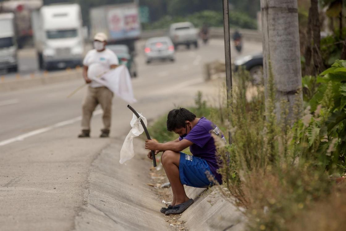 Un niño ondea una bandera blanca en la carretera pidiendo ayuda por hambre debido a la crisis economica provocada por el coronavirus, en Guatemala. EFE/ Esteban Biba/Archivo