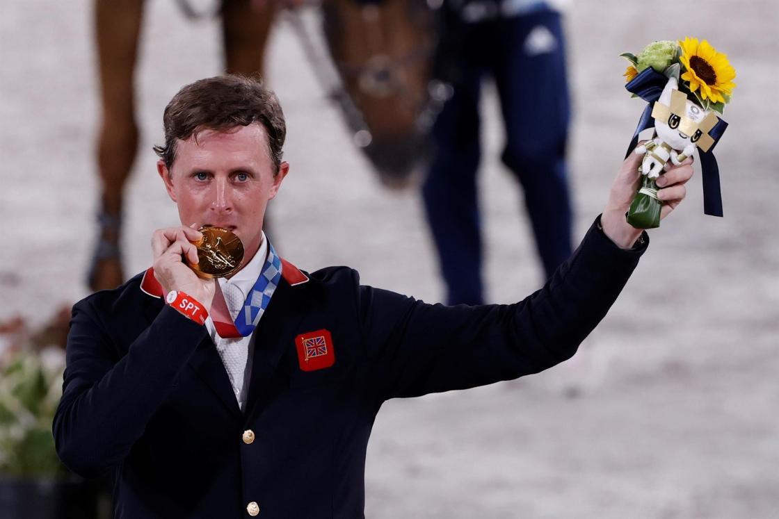 El británico Ben Maher celebra en el podio tras conseguir la medalla de oro en la final de salto individual de Equitación durante los Juegos Olímpicos 2020, este miércoles en el hipódromo Equestrian Park en Tokio (Japón). EFE/ Kai Försterling
